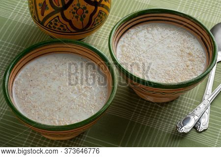 Traditional ceramic bowl with Moroccan belboula saikouk, barley grits, on the table