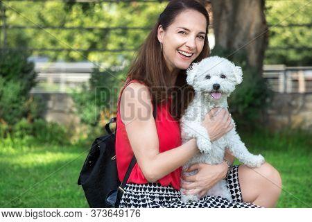 Portrait Of A Woman Holding A Little Dog, Bichon Frise, Outdoors At A Park.