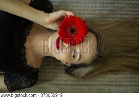Portrait Of A Girl With A Red Gerbera Flower.