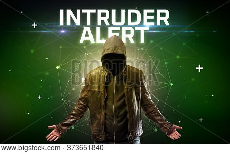 Mysterious hacker with INTRUDER ALERT inscription, online attack concept inscription, online security concept