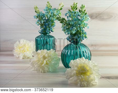 Two Teal Green Glass Vases Filled With Teal Hydrangea Flowers With White Carnation Flower Blooms Lin