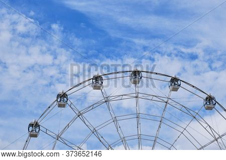 Part Of A Ferris Wheel With Cabs On Background Of A Beautiful Cloudy Sky. Copy Space.