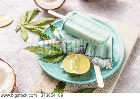 Ice Cream Popsicle Bars With Coconut Slices, Cannabis On Concrete Background. Ice Cream Popsicle Bar