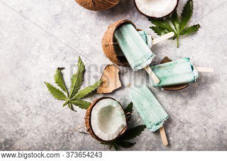 Ice Cream Popsicle Bars With Coconut Slices, Cannabis On Concrete Background.  Hemp Ice Cream Popsic