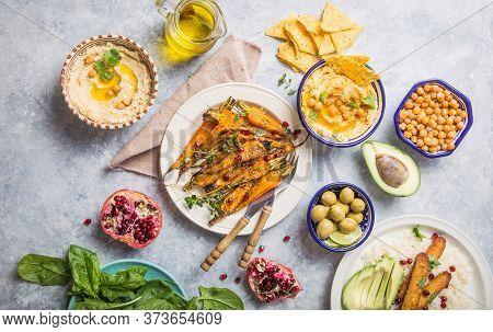 Variety Of Healthy Vegan Snacks, Gourmet Dips. Hummus,  Roasted Carrots, Rice With Tempeh In Ceramic