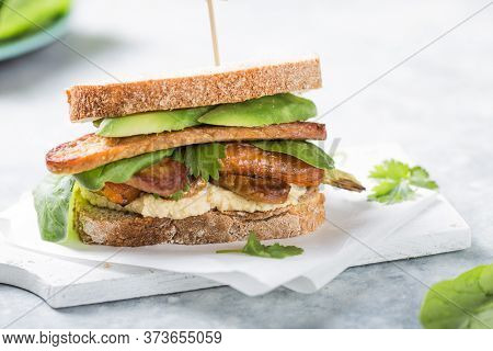 Tempeh And Kale Sandwich With Hummus, Spinach And Avocado  On Table. Sandwich With Hummus,