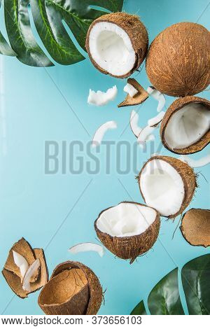 Halves Of Coconut, Open Coconut Cut In Half Isolated On Blue Background. Coconut Pulp Is Very Health