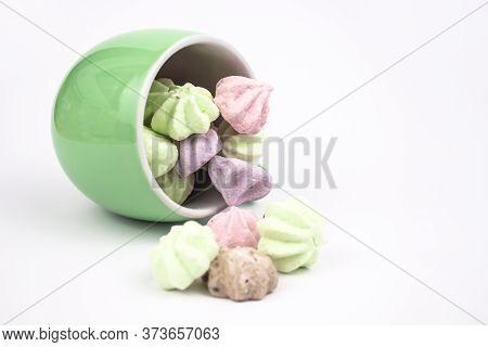 Meringue On A White Background. Multi-colored Meringues In A Green Cup On A White Background. Mering