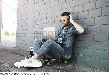 Young Man With Headphones Using Laptop In The Street - Trendy Cool Guy Having Fun Surfing Online And