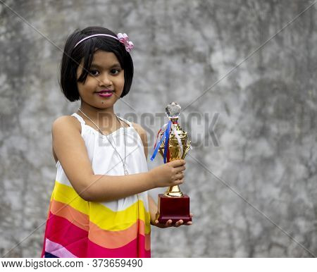 A Golden Color Winner Trophy Held In Hand By An Cute Indian Girl Child With Selective Focus