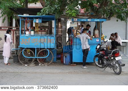 Traditional Tea House In The Streets Of India. Tea Vendor Preparing Tea And Buyer Maintaining Distan
