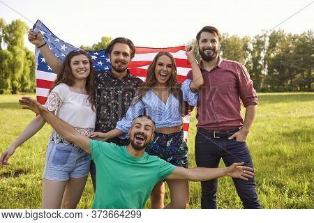 Patriotic Celebration Of Independence Of America On July 4. Friends Smiling With America Flag Celebr