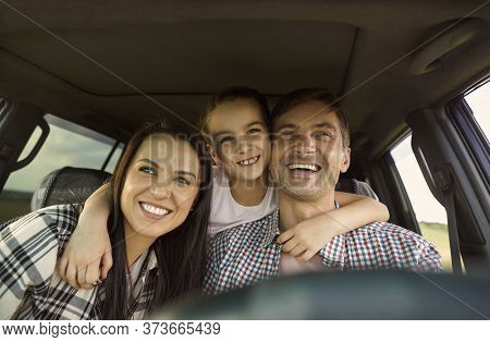 Happy Family Travels By Car In Summer. Adorable Girl Embracing Her Parents While Sitting Inside Car