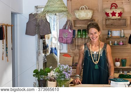 Portrait Of French Blonde Mature Woman Smiling In Her Handmade Gifts Store In France, Entrepreneur C