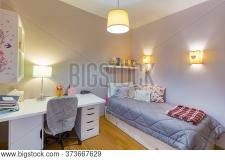 Cozy Interior Bedroom Of A Young Woman With White Laminate Desk, A Desk Chair With Wheels, Single Be