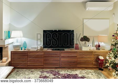 A Modern Large Wooden Cabinet With A Flat Tv Placed On A Living Room With A Christmas Tree.