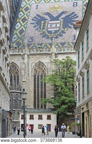 Vienna, Austria - July 12, 2015: People Walking Around St. Stephen Cathedral With Big Coat Of Arms A
