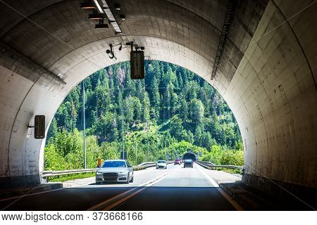 Road Tunnels In Alpine Mountains, Switzerland. Inside The Modern Tunnel And View Of Entrance To Next
