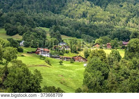 Landscape Of Alpine Mountains, Small Village In Switzerland. Scenery Of Alps And Houses In Countrysi
