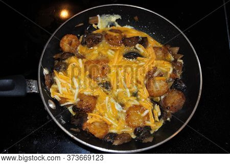 Cooking Mushrooms Onions Hash Browns And Cheese In A Frying Pan With Oil Seasoning And Steam