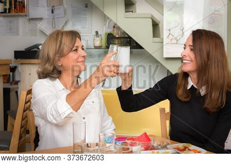 A Senior Woman 61 Years, Toasting With Her Mature Friend, 46, With A Glass Of Ouzo, Greek Beverange,