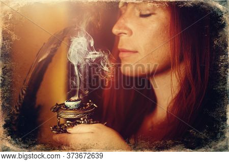 Incense In A Woman Hand, Incense Smoke On A Blur Background. Old Photo Effect.