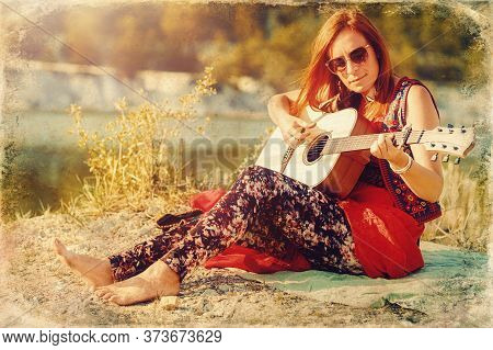 Beautiful Woman Playing With Guitar In Nature. Old Photo Effect.