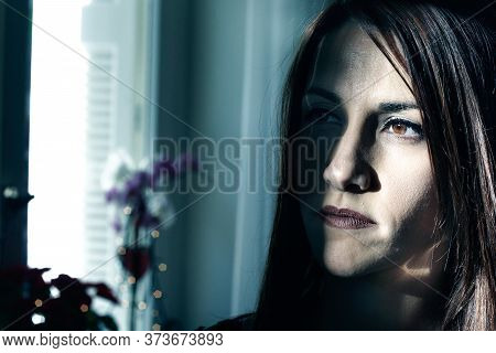 Portrait Of A Young Woman Looking Away Expressing Lonliness, Pensive, Low Key Light.