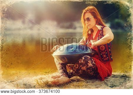 Beautiful Woman Playing With Hangdrum In Nature. Old Photo Effect.