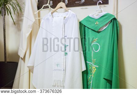 Liturgical Clothing And Vestments Of The Priest Hang On Wall Clothes Horse. Selective Focus