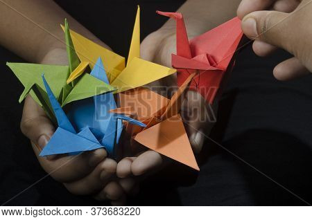 Young Girl With Origami Paper Crane (birds) In Hand Makes A Wish. Inspired By The Japanese Legend Th