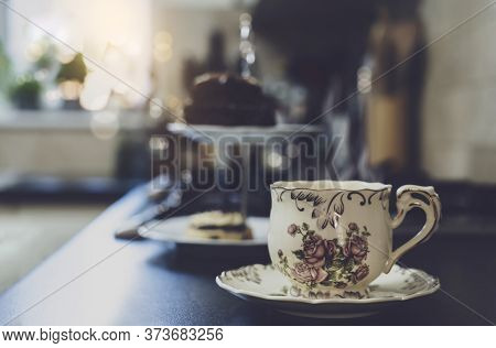 Hot Cup Of Tea With Blurry Cake On Hight Tea Stand In The Kitchen Background. Cup Of Aroma Dring Wit