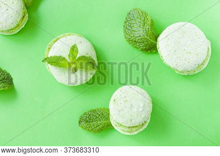 Macaroons. Green Macaroons On A Green Background With Mint.