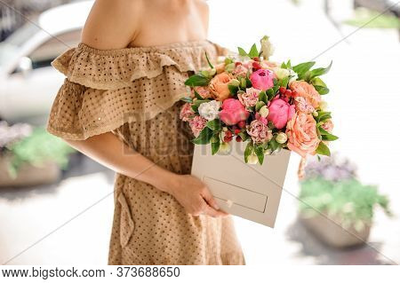 Young Woman Neatly Holds White Square Box With Flowers Of Different Colors.