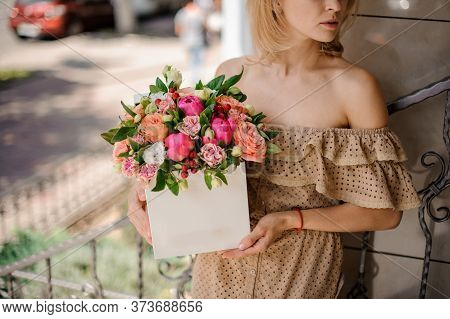 Young Woman Neatly Holds In Her Hands White Square Box With Flower Arrangement
