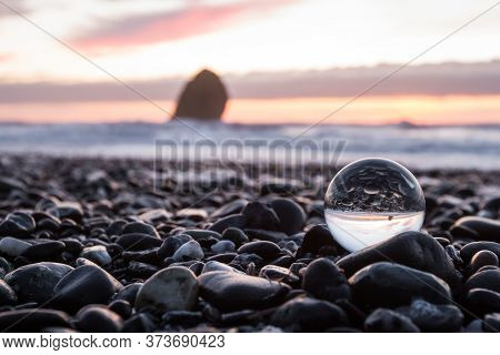 Coastal Sunset Inverted On A Clear Glass Sphere Using A Wide Angle Lens To Capture A Slightly Blurre
