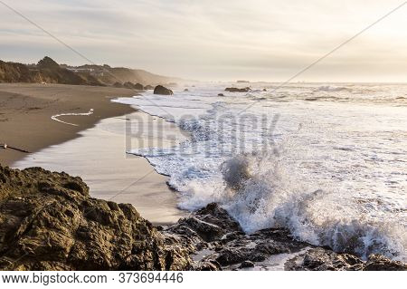 Waves Crashing Into The Rocky Shoreline In Nesika Beach, Oregon Late In The Afternoon With The Sun A