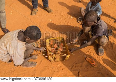 Bissau, Guinea-Bissau - January 5, 2020: group of African Kids playing with a made toy, in rural Guinea-Bissau