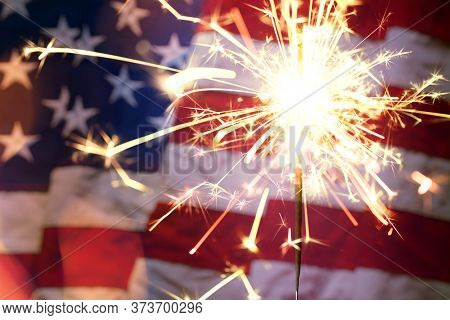 Burning sparkler with hot glowing embers in front of US American flag for 4th of July.