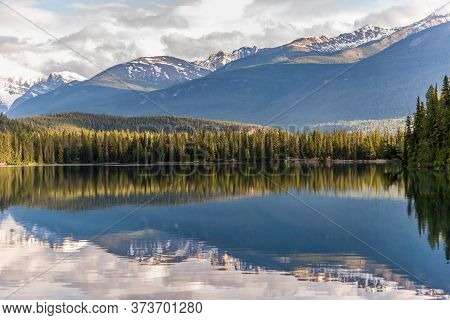 Mountain And Lake With Reflection And Colourful Chairs In Jasper Canada