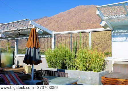 June 22, 2020 In Palm Springs, Ca:  Outdoor Deck Furniture Including Umbrellas And Poolside Chairs B
