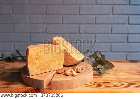 A Head Of Aged Cheese Cut In Half On A Wooden Board