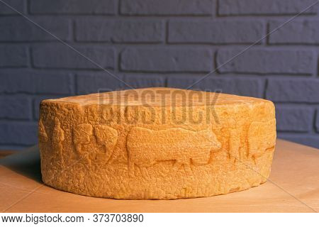 Swiss Cheese On A Wooden Stand Against A Brick Wall.
