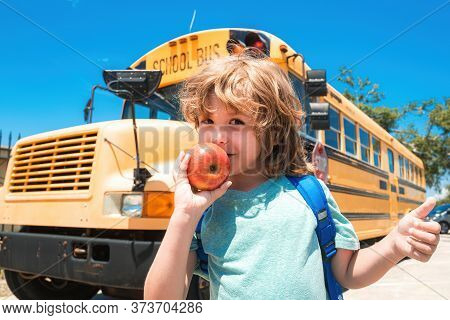 Child From Elementary School With Bag On School Bus Backgroung. School Boy At The Front Of The Schoo
