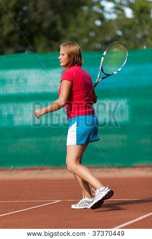 Young Woman Playing Tennis On A Dross Field