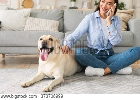 Everyday Life Concept. Casual Girl Talking On Cell Phone And Caressing Labrador, Sitting On The Floo