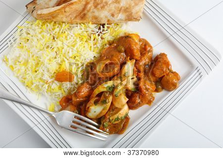 Chicken jalfrezi curry on a plate with pilau rice, a piece of naan bread and a fork from above.