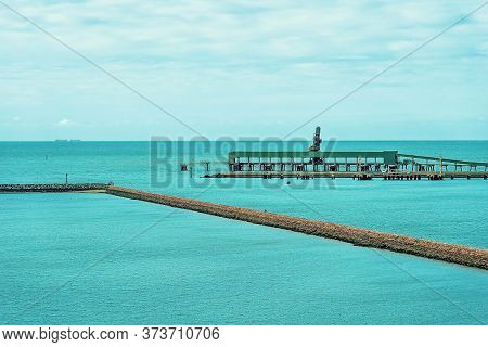 Industrial Wharf With Ship Loading Facilities Beside A Marina Stone Wall In A Wide Blue Ocean