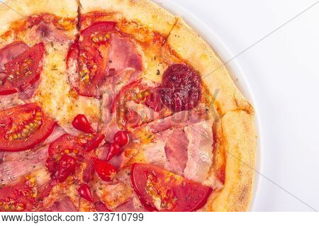 Tasty Pizza On A White Plate With Tomatoes And Ham. Italian Food Isolated On The White Background