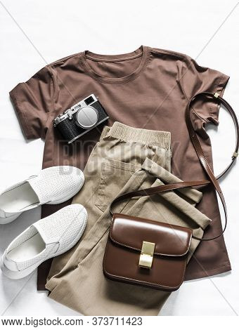 Brown T-shirt, Cotton Joggers Jeans, White Sneakers, Leather Cross Body Bag And Camera On A Light Ba
